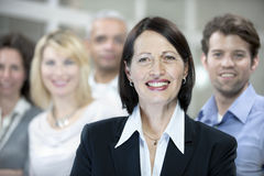 Mature businesswoman and business team Stock Images