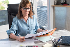 Mature businesswoman checking documents Royalty Free Stock Image