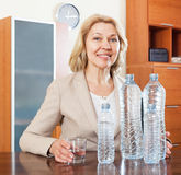 Mature businesswoman with clean water at table Stock Image