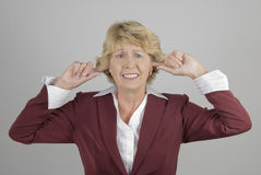 Mature businesswoman with fingers in ears. Studio shot of smartly-dressed mature businesswoman with her fingers in her ears. Can't stand the noise or refusing to Royalty Free Stock Photography