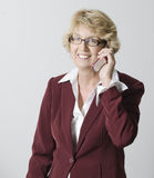 Mature businesswoman on her cellphone. Confident, smiling mature businesswoman receiving a call on her cellphone royalty free stock photos