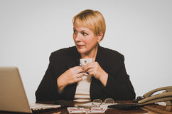 Mature businesswoman hides money Royalty Free Stock Photography