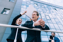 Mature businesswoman holding folder and hitting businessman outside office building stock photography