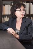 Mature Businesswoman Looking to the Side. Businesswoman in glasses with a background of books and papers looking at something beyond the frame Royalty Free Stock Photos
