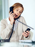 Mature businesswoman multitasking by handling Royalty Free Stock Photography