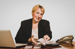Mature businesswoman offering money Royalty Free Stock Images