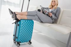 Businesswoman waiting for trip. Mature businesswoman reading magazine while waiting for trip Royalty Free Stock Images
