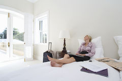 Mature businesswoman sitting on bed with laptop, looking out window Royalty Free Stock Images