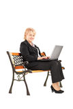 Mature businesswoman sitting on a wooden bench and working Royalty Free Stock Photography