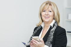 Mature businesswoman with smart phone Royalty Free Stock Photography