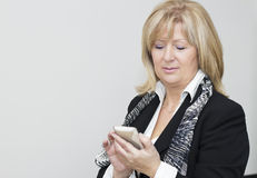 Mature  businesswoman with smart phone Stock Image