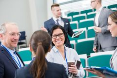 Businesswoman Smiling While Communicating With Colleagues stock photography