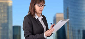 Mature businesswoman taking notes. With background of business center Royalty Free Stock Photos