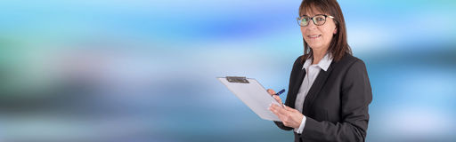 Mature businesswoman taking notes. On blurred background Royalty Free Stock Photos