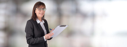 Mature businesswoman taking notes. On blurred background Stock Images