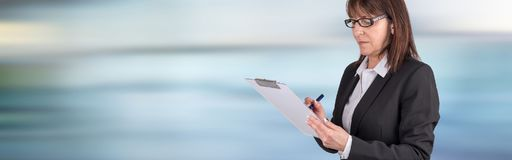 Mature businesswoman taking notes. On blurred background Stock Image