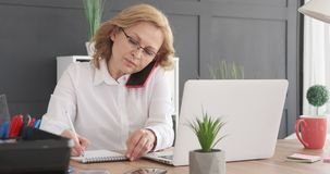 Businesswoman talking on phone and writing notes at office stock footage