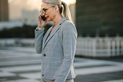 Mature businesswoman on way to home using phone stock images