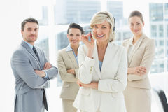 Mature businesswoman wearing headset with colleagues in office Royalty Free Stock Images