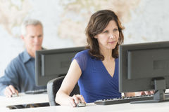 Mature Businesswoman Working On Computer At Office Stock Photos