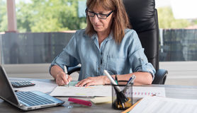 Mature businesswoman working on documents Royalty Free Stock Images