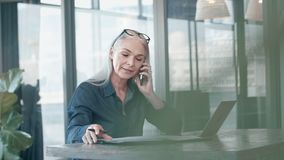 Mature businesswoman working at her office desk. Mature business woman talking on cell phone while working on laptop and doing paperwork in office. Senior female stock footage