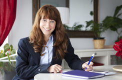 Mature Businesswoman working at home. Smiling. Mature Businesswoman working at home. Studying. Smiling stock photography