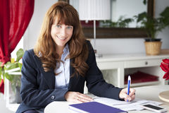Mature Businesswoman working at home. Smiling. Mature Businesswoman working at home. Studying. Smiling stock photos