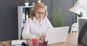 Mature businesswoman working on laptop stock video footage