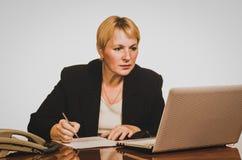 Mature businesswoman writes Stock Photography