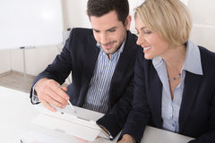 Mature businesswoman and young businessman working together. Stock Image