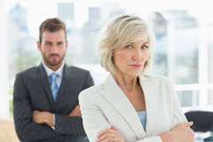 Mature businesswoman and young man with arms crossed Royalty Free Stock Image