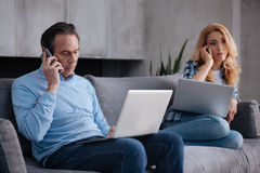 Mature busy couple using electronic gadgets indoors Stock Photography