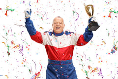 Mature car racing champion holding a trophy. Delighted mature car racing champion holding a trophy and celebrating with confetti streamers around him stock photography