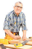Mature carpenter measuring a plank Stock Photos