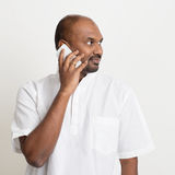 Mature casual business Indian man talking on phone. Portrait of mature casual business Indian man calling on smartphone, standing on plain background with shadow Royalty Free Stock Photography