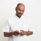 Mature casual business Indian man texting using smartphone Royalty Free Stock Photo