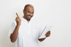 Mature casual business Indian man using tablet pc and credit car Stock Photography
