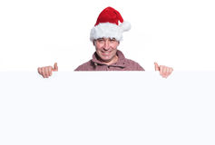 Mature casual man in santa hat is holding a big blank board Stock Image