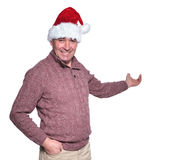 Mature casual man in santa hat is presenting Stock Images