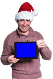 Mature casual man wearing santa hat is showing a pad Royalty Free Stock Images