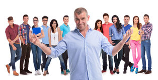 Mature casual man welcoming to his young team stock image