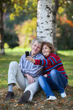 Mature Caucasian couple making selfie by cellphone in autumn park Stock Photography
