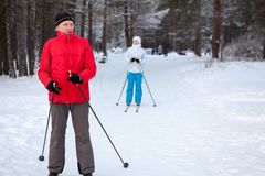 Mature Caucasian father with adult daughter skiing on cross country skis in winter race track in woods Stock Photos