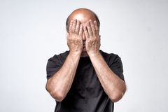 Mature caucasian man in black t-shirt covering his face with hands over gray background. Royalty Free Stock Photography