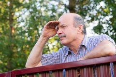 Mature caucasian man carefully watching over the fence. Concept of curious neighbors and private life royalty free stock photos