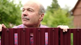 Mature caucasian man carefully watching over the fence. Curious neighbors and private life. Mature caucasian man carefully watching over the fence. Concept of stock footage