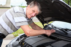 Mature Caucasian man checking oil level in car Royalty Free Stock Photography