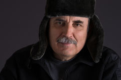 Mature Caucasian man in fur-cap against dark background Royalty Free Stock Image
