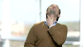 Mature caucasian man having neck ache. Male european office worker suffering from neck pain. Blurred window background stock video